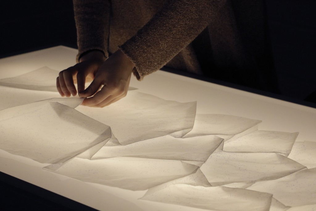 A close up of a student's hands carefully folding glassine paper over top a light box.